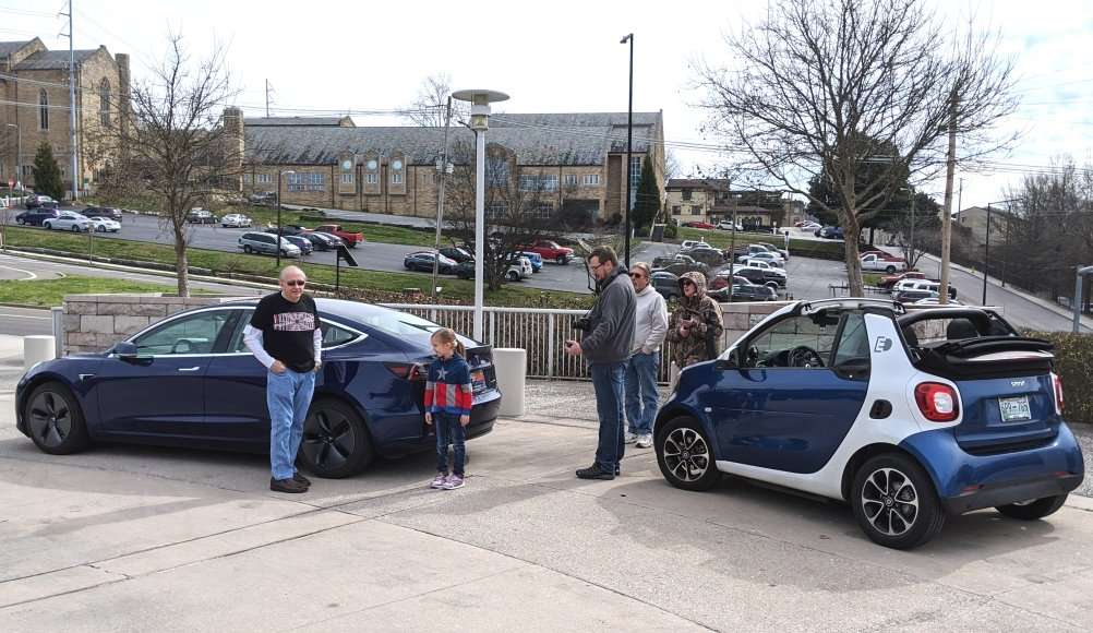 Ride and Drive: People standing near Tesla Model 3 and SMART EV car