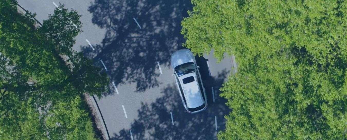 Car driving through shaded road, no text